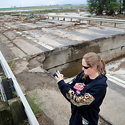 LONGMONT, CO - SEPTEMBER 13: Leah Sorber of Longmont, Colorado takes pictures of the flooding and damage on a partially collapsed bridge on Weld County Road 1 in Longmont, Colorado as heavy rains for the better part of week fueled widespread flooding in numerous Colorado towns on September 13, 2013. Sorber moved to Colorado after losing her home in to a flood in Minnesota years ago. (Photo by Marc Piscotty/ © 2013)