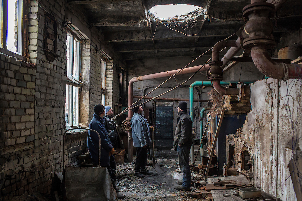 Vladimir Vertsanov, Danil Goncharenko, Petro Goncharenko, and Vladimir Iermilov, from left, take a break from shoveling coal for heating at the village school to gaze at a hole punched in the ceiling of the boiler room by a rocket the previous year on Thursday, February 11, 2016 in Troitske, Ukraine.