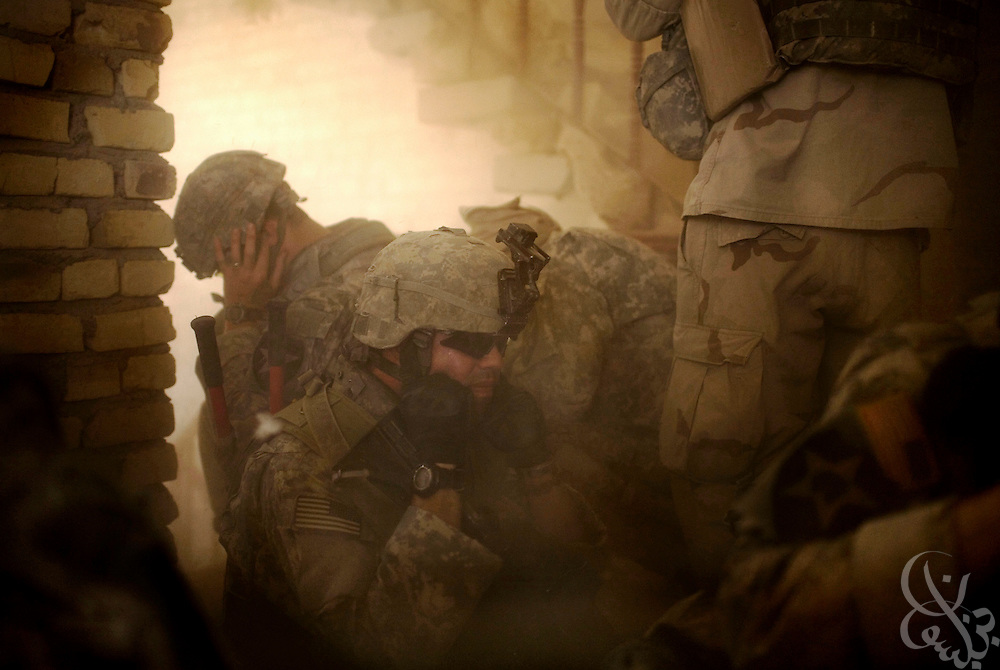 U.S. Army 1-23 Stryker soldiers brace themselves and plug their ears during a loud, controlled explosion of multiple roadside enemy bombs discovered just outside their stronghold position inside an Iraqi house during a clearing operation June 23, 2007 in Baquba, Iraq.