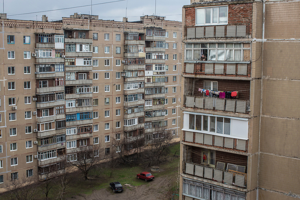 A man smokes a cigarette on his balcony in an apartment building overlooking a hill from which Ukrainian forces shelled the city when it was controlled by Russian-backed rebels on Monday, March 28, 2016 in Slovyansk, Ukraine. The building from which the picture was shot was hit by a shell, killing a woman.