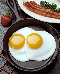 breakfast two fried eggs black cast iron fry pan sunny side up whole fresh strawberry two strip bacon garnish parsley