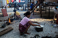 A Bajau woman cooking rice and vegetables for her family