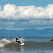 Two surfers enjoy a small swell at the mouth of the Lyre River about 15 miles west of Port Angeles, WA on the Strait of Juan de Fuca. Yes, you can surf 50 miles from the ocean! With just the right angle swell, really large waves barrel down the Strait from the north Pacific, and overhead surf isn't unheard of. In the background here is Vancouver Island, BC about 25 miles across the Strait.