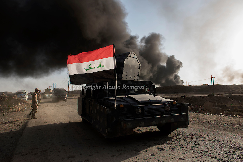 Iraq, Qayyara: Iraqi army armoured vehicle in Qayyara where is visible the smoke of the crude oil fields that IS fighters set on fire as they retreated from the city. Alessio Romenzi