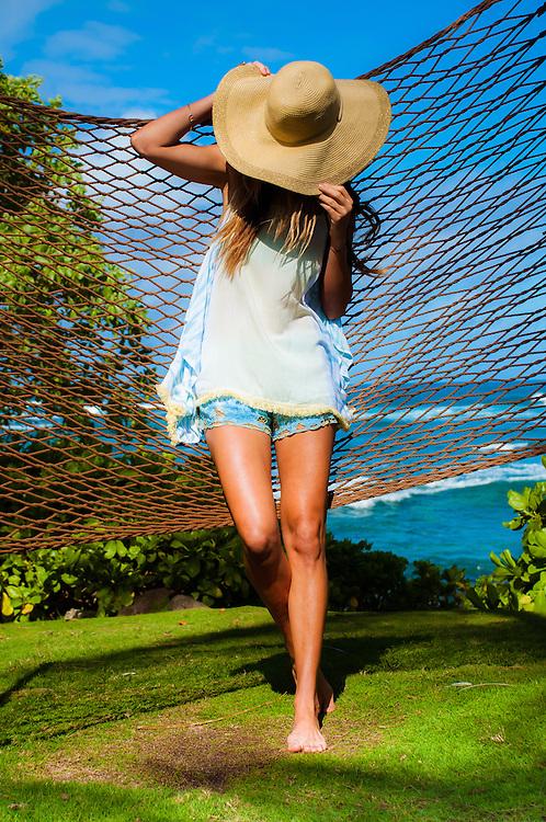 Woman in hammock by the beach at Turtle Bay in Hawaii wearing shorts and tank top by Tiare Hawaii. <br /> www.tiarehawaii.com<br /> Model Andrea Hannemann