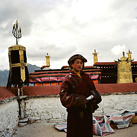 A young Buddhist monk stands on the roof of the Jokhang Temple in Lhasa, the capital of Tibet in western China. (Photo/Scott Dalton)