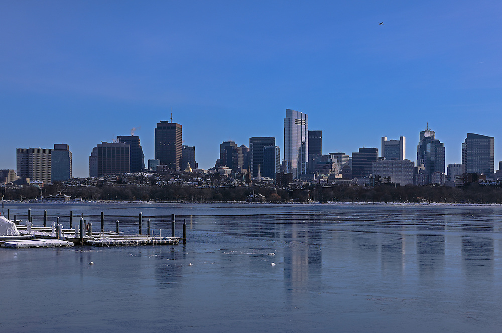 Winter in Boston skyline photography reflected in a frozen Charles River featuring iconic building and some of the tallest skyscrapers in Boston such as the Boston State Street Corporation, The Federal Reserve Bank of Boston, the Millennium Tower and the One Financial Center at Dewey Square on a bitter cold morning in winter. Boston winter photos are available as museum quality photography prints, canvas prints, acrylic prints, wood prints or metal prints. Fine art prints may be framed and matted to the individual liking and decorating needs at<br />  <br /> http://juergen-roth.pixels.com/featured/leaving-boston-juergen-roth.html<br /> <br /> All photographs are available for digital and print image licensing at www.RothGalleries.com. Please contact me direct with any questions or request.<br /> <br /> Good light and happy photo making!<br /> <br /> My best,<br /> <br /> Juergen<br /> Prints: http://www.rothgalleries.com<br /> Photo Blog: http://whereintheworldisjuergen.blogspot.com<br /> Instagram: https://www.instagram.com/rothgalleries<br /> Twitter: https://twitter.com/naturefineart<br /> Facebook: https://www.facebook.com/naturefineart