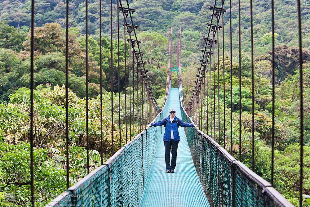 A young woman above the Costa Rica Cloud Forest canopy on a walking bridge in the Monteverde Cloud Forest Reserve in Selvatura Adventure Park, Costa Rica