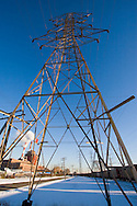 A high tension tower carrying power transmission lines stretches toward the sky near a power plant in Hammond, IN.