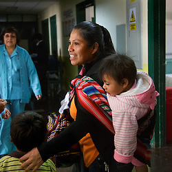 Nurse Carmen Gonzales Zapata approaches Delia Maqquerbua Ballỏn and her sons Lucas, 4, and Lucero, 1, as they wait in the hallway of the Hospital Regional del Cusco burn unit.