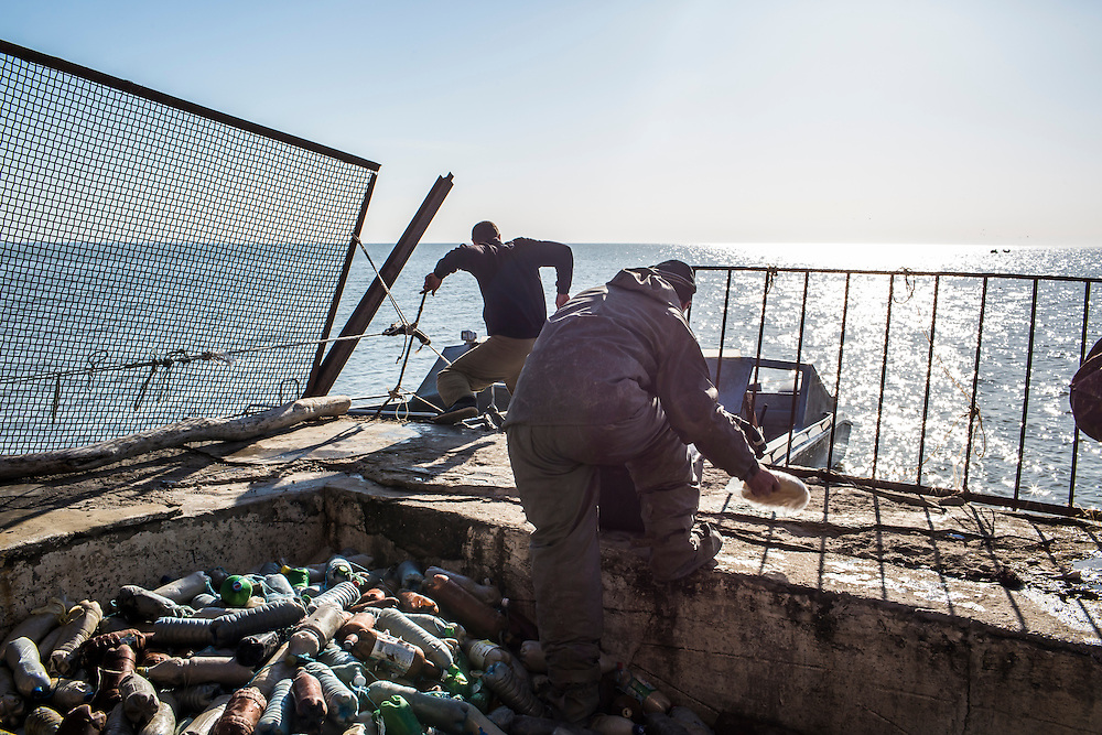 Fishermen climb out to their boat on the Sea of Azov on Saturday, April 11, 2015 in Siedove, Ukraine.