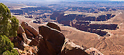 The White Rim Road winds across a shelf in Canyonlands National Park, as seen from Grand View Point Overlook on Island in the Sky, above Colorado River canyons, in Utah, USA. (Panorama stitched from 3 photos.)