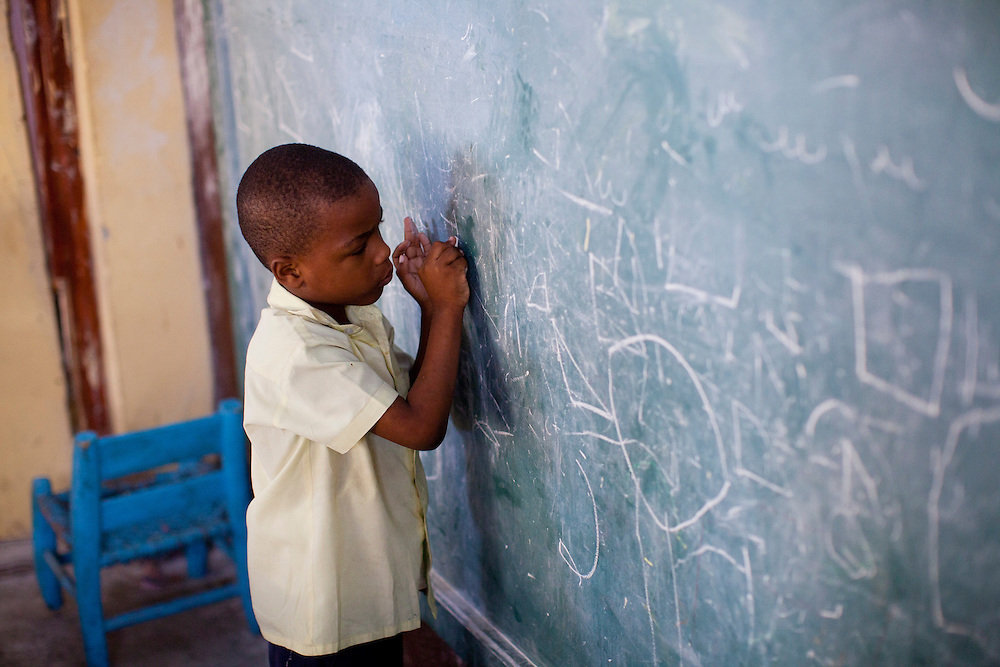 A boy writes on the chalkboard at a public school on July 7, 2010 in Port-au-Prince, Haiti. Most schools in Port-au-Prince didn't open until April, three months after the earthquake.