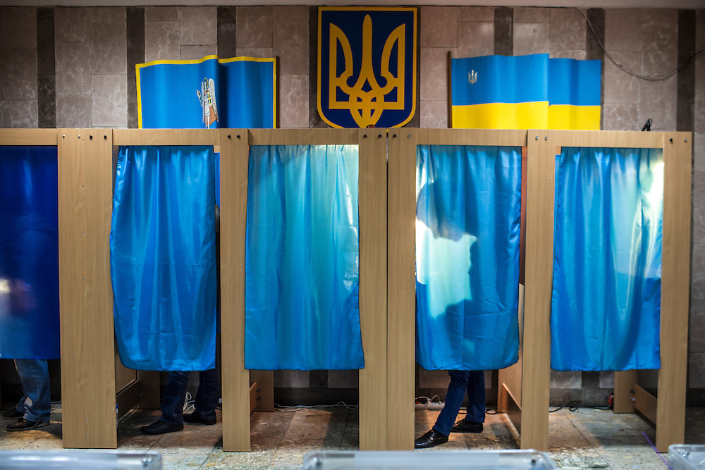 KIEV, UKRAINE - OCTOBER 26: Voters fill out their ballots for parliamentary elections in voting booths at a polling station on October 26, 2014 in Kiev, Ukraine. Although a low turn out is expected in the east of the country, amid continued fighting between Ukrainian forces and pro-Russian seperatists, Ukraine is expected to elect a pro-western parliament in a further move away from Russian influence. (Photo by Brendan Hoffman/Getty Images) *** Local Caption ***