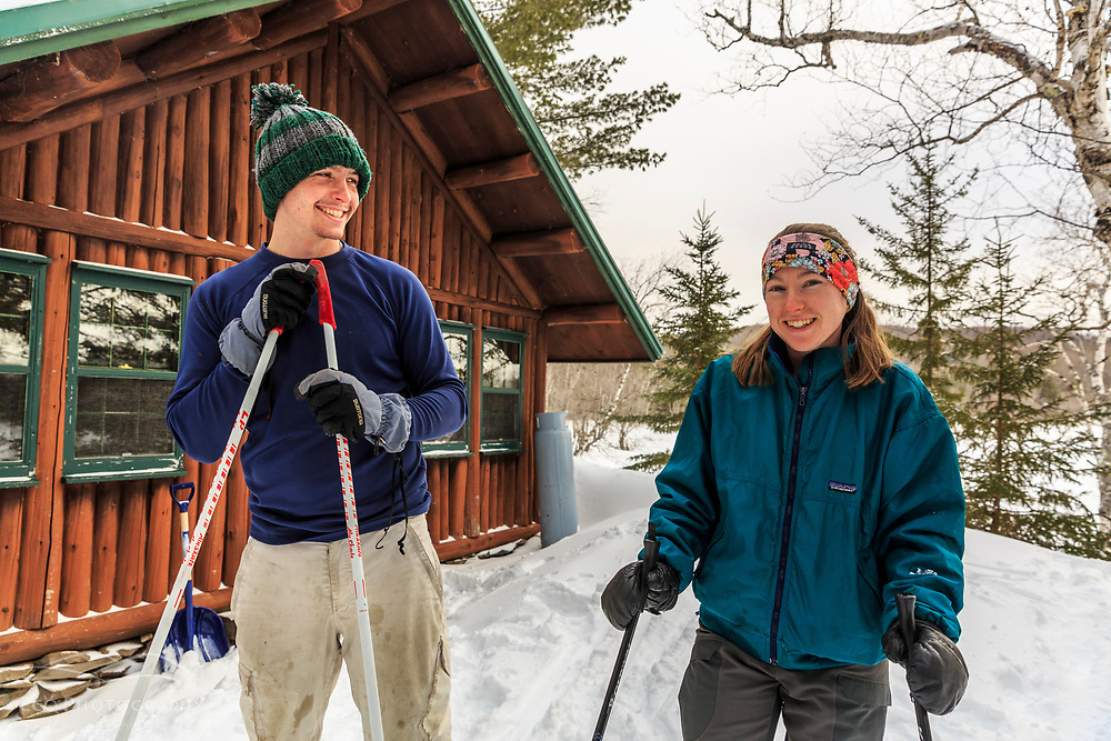 A couple on cross country skis outside Haskell Hut in Maine's Katahdin Woods and Waters National Monument. East Branch of the Penobscot River is in the background.