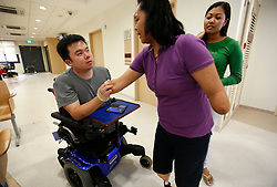 Aishah and fellow sportsman Jason Chee greets each other at Tan Tock Seng Hospital in Singapore 25 June 2014. A navy serviceman, Chee lost his three limbs in a ship accident but inspired by Aisha's story and encouragement, moved on to return to work and took up table tennis to win a bronze team medal in the ASEAN Para games this year.