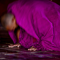 A Buddhist monk bowing in prayer in a monastery in Ladakh.