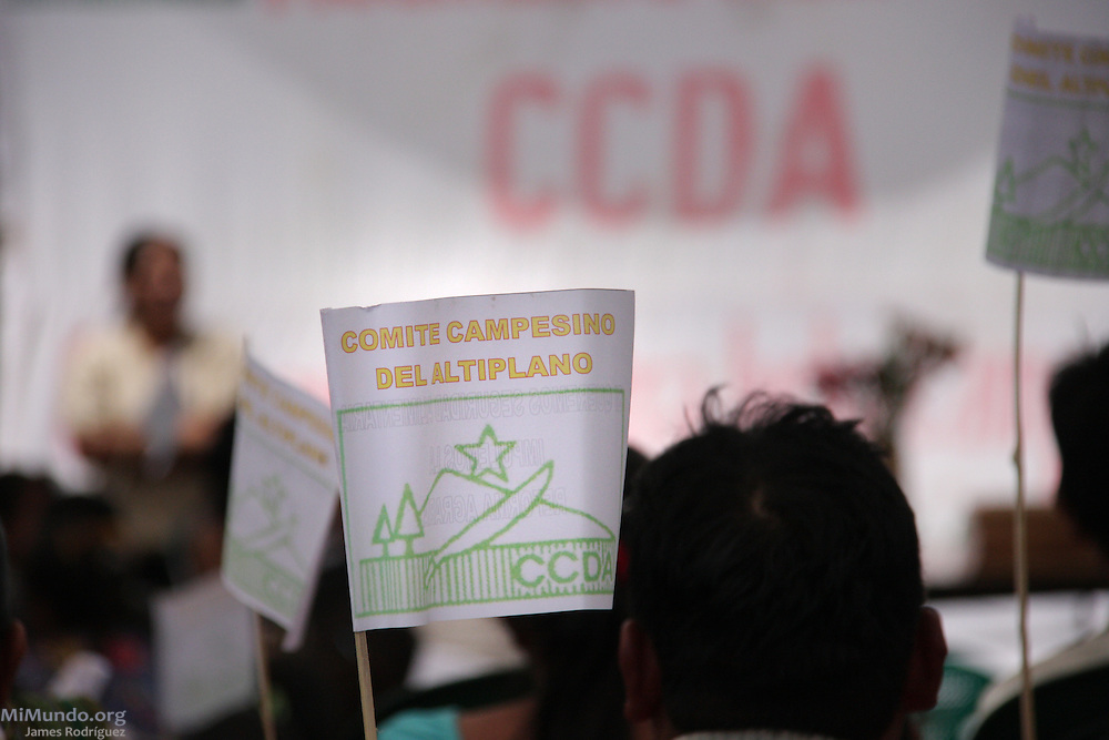 People affiliated to the Campesino Committee of the Highlands (CCDA, in Spanish) wave flags and listen to speeches during the CCDA's annual meeting. The CCDA was founded in 1982 as an organization that works to defend the rights of workers on large coffee, sugar and cotton plantations, to recover lands taken from the Mayan communities over the past centuries, and to promote and recover Mayan culture and spirituality. Today about 100 communities in 11 Guatemalan provinces are affiliated to the CCDA, but the organization is strongest in the Madre Vieja valley of Sololá. Quixaya, San Lucas Toliman, Solola, Guatemala. March 2, 2010.