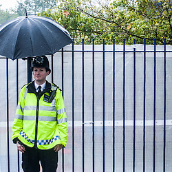 London, UK - 25 August 2014: a police officer protects himself from the rain during the Notting Hill Carnival in London.