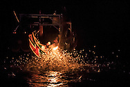 Hundreds of fish leap out of the water, attracted by the flame. Fishermen wait with nets to catch them.