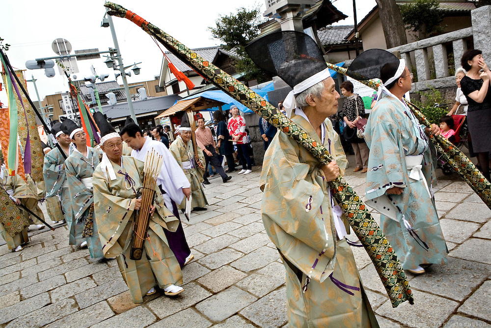 People dressed in traditional costumes carrying the bows and arrows of the Yabusame archers, during the second day of the 3-day anual festival of Tsurugaoka Hachimangu Shrine in Kamakura.