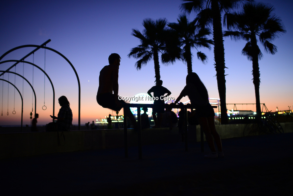 Young people practicing calisthenics at night in Santa Monica, California.