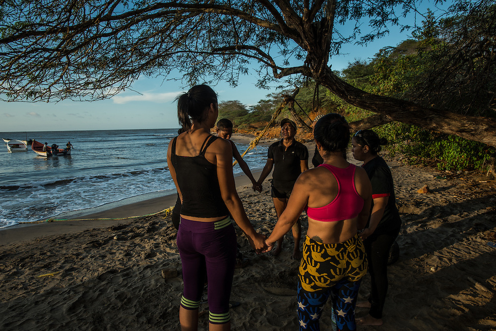FALCÓN, VENEZUELA - SEPTEMBER 26, 2016: Maria Piñero and other undocumented migrants joined hands and prayed together on the beach for safety during their difficult and risky journey, just before boarding the smuggler's boat that will illegally take them from Venezuela to Curaçao.  Ms. Piñero was very afraid, but was determined to make the trip and make a better life for herself and her family in Curacao.  Undocumented migrants here have mortgaged property, sold kitchen appliances and even borrowed money from the same smuggling rings that pack them on the floorboards alongside drugs and other contraband. The journey to Curaçao takes them on a 60-mile crossing filled with backbreaking swells, gangs of armed boatmen and coast guard vessels looking to capture migrants and send them home. Then, after being tossed overboard and left to swim ashore, they hide in the brush to meet contacts who spirit them anew into the tourist economy of this Caribbean island. They clean the floors of restaurants, work in construction, sell trinkets on the street, or even solicit Dutch tourists for sex. But at least, the migrants say, there is food. PHOTO: Meridith Kohut