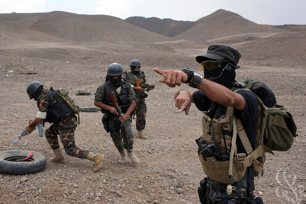 A trainer orders members of the Yemen Special Forces Counter-Terrorism squad to run to the next firing point during a live-fire drill at a training range on the outskirts of Sana'a, Yemen April 14, 2010. Yemen continues efforts to improve the quality of its' armed forces as it faces a Houthi rebel movement in the North, a  separatist movement in its Southern territory, and Al Qaeda terrorist activity.