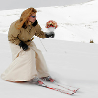 Rachina Allen skis down a mountain clutching her bouquet and wedding dress after her mountaintop wedding to Steve Allen at the Loveland ski area near Georgetown, Colorado February 14, 2005.  In a Valentines Day tradition more than 50 couples were wed on the Continental Divide at 12,440 feet.   REUTERS/Rick Wilking