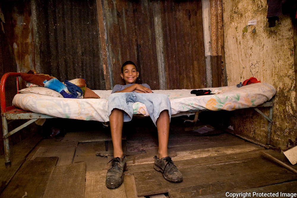Daniel, Kevin's little brother (8 years old) sits on his bed in the home he shares with his older brother and mother in San Felipe.