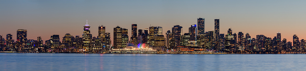 The lights of the city of Vancouver's downtown at sunset. Buildings here include Canada Place, Harbour Center, the Convention Center, Shangri-La, and Trump Tower.  Photographed from the Burrard Dry Dock Pier (near Londsdale Quay) in North Vancouver, British Columbia Canada across Burrard Inlet from Vancouver.