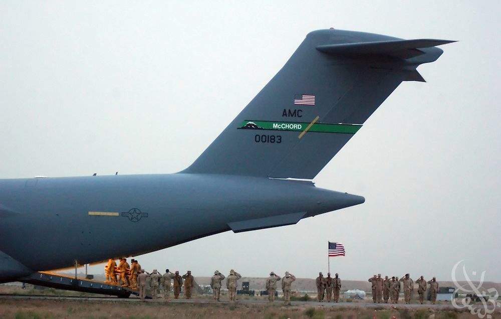 The bodies of U.S. Air Force Tech. Sgt. Sean M. Corlew, U.S. Army Staff Sgt. Anissa A. Shero and U.S. Army Green Beret Sgt. 1st Class Peter P. Tycz II are carried one by one onto an airforce C-17 aircraft for repatriation June 16, 2002 at Bagram airbase in Afghanistan. Corlew, Shero and Tycz were killed when the Airforce MC-130 aircraft that they were flying crashed June 13, 2002 after takeoff at a forward airstrip south of Gardez, Afghanistan.