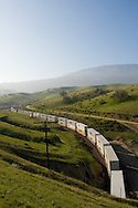 Curving through the spring-green hills of the Tehachapi Mountains in Southern California, a train of all white Swift Trucking intermodal containers navigates the joint Union Pacific/BNSF mainline.
