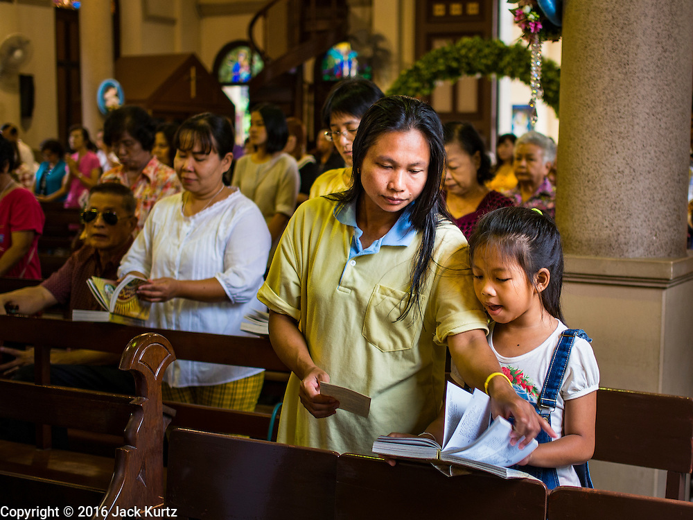27 MARCH 2016 - BANGKOK, THAILAND:  A woman opens her daughter's hymnal during Easter services at Santa Cruz Church in Bangkok. Santa Cruz was one of the first Catholic churches established in Bangkok. It was built in the late 1700s by Portuguese soldiers allied with King Taksin the Great in his battles against the Burmese who invaded Thailand (then Siam). There are about 300,000 Catholics in Thailand, in 10 dioceses with 436 parishes. Easter marks the resurrection of Jesus after his crucifixion and is celebrated in Christian communities around the world.     PHOTO BY JACK KURTZ