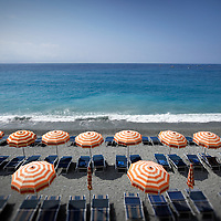 A beach in Monterossa, Italy, with colorful striped umbrellas.