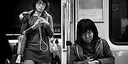 Taipei MRT.  A young woman napping while another enters the carriage.