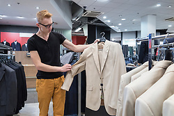 Teenager boy choosing jacket in retail shop Tartu Kaubamaja in Estonia.