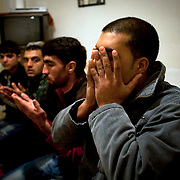 Local Afghani's who have been living in Pamphila, a town 10 minutes out of the main city Mytilene pray in their home.  Image © Angelos Giotopoulos/Falcon Photo Agency..