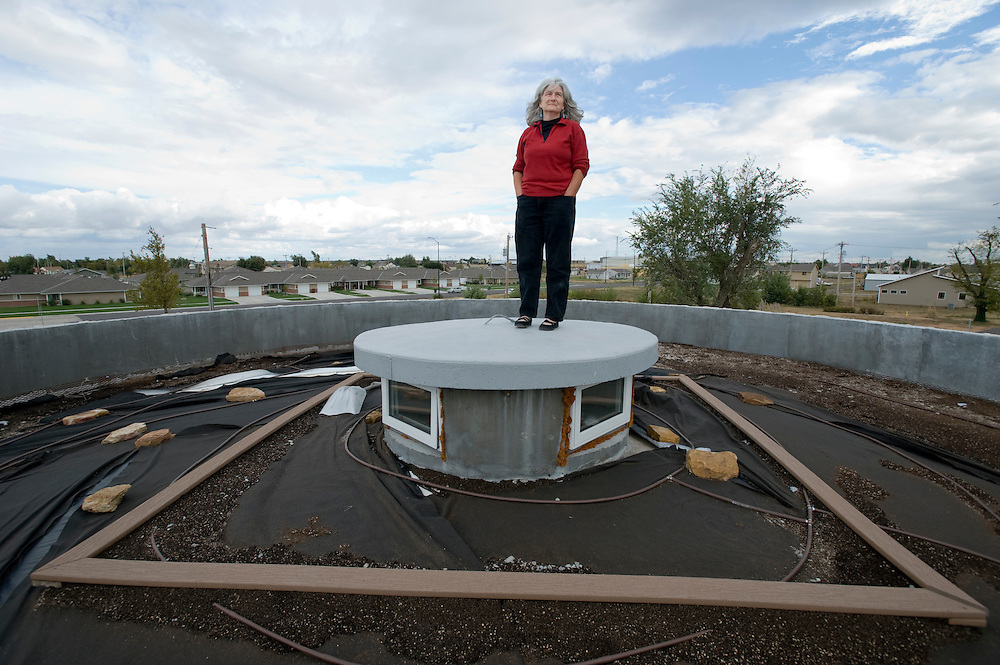 "Greensburg, Kansas, USA..Catherine Hart, program director of Greensburg GreenTown, on the -soon to be green - roof of The Greensburg Silo Home. ..With precast concrete walls and a cylindrical form, this house will stand up to very strong winds. It also has a LEED rating of level 47. The Greensburg Silo Home is a part of The Chain of Eco-Homes--a series of twelve green houses that will serve as ""living laboratories"" featuring all types of building techniques, energy efficiency features, and green living products. Each will be available both as an informational center and as eco-lodging where people can experience green living first-hand...Greensburg GreenTown is a grassroots community-based organization which has worked side-by-side with city and county officials, business owners and local residents to incorporate sustainable principles into their rebuilding process. GreenTown serves as an educational resource for the community, a conduit through which donations can be distributed, and a representative to those outside the community who are interested in the Green Initiative...""Greensburg: Better, Stronger, Greener!"".On May 4, 2007, an EF5 tornado cut a 1.7-mile path of destruction through Greensburg, Kansas. Winds reaching speeds of 205 miles per hour uprooted trees, demolished homes and leveled the town. Eleven people died and 95% of the buildings were destroyed beyond repair. Residents have since worked furiously to rebuild it in a way that is both economically and environmentally sustainable and to meet the highest environmental standards. Greensburg, whose population has dropped from about 1400 to 800 following the storm and is now growing again, is currently the greenest town in America and the first in the United States to pass a resolution to certify that all city-owned buildings earn LEED Platinum accreditation, the highest level of the LEED rating system...Foto © Stefan Falke"