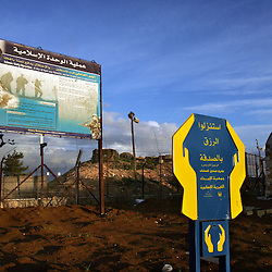 A martyr poster of Abdullah Atwi, a Hezbollah fighter, is seen at the site where he blew himself up in 1988 during a fight against the Israelis in Kfar Kila, Lebanon, March 10, 2005. Directly behind the poster is the Israeli border and checkpoint. Earlier in the week hundreds of thousands of pro-Syrian protesters answered the nationwide call from Hezbollah, the militant Shiite Muslim group, to demonstrate against foreign intervention.