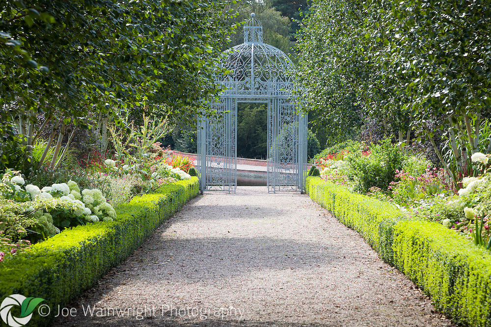 This wrought iron gazebo was produced at Siddington Smithy, near Capesthorne Hall, Cheshire.  This  mellow September scene shows the borders at their late summer best.