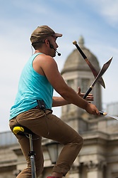 """London, July 18th 2015.  Canadian Unicyclist and juggler """"Dynamike"""" entertains the crowd in Trafalgar Square as part of the Busk in London Festival aimed at showcasing the outstanding talents of many of the capital's finest street performers, including, musicians, magicians, living statues and bands."""