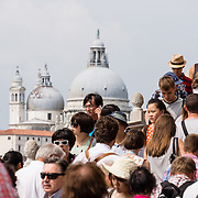 "Crowds of people near Saint Mark's Square, across from Basilica di Santa Maria della Salute. Venice (Venezia) is the capital of Italy's Veneto region, named for the ancient Veneti people from the 900s BC. The romantic ""City of Canals"" stretches across 100+ small islands in the marshy Venetian Lagoon along the Adriatic Sea in northeast Italy, between the mouths of the Po and Piave Rivers. The Republic of Venice was a major maritime power during the Middle Ages and Renaissance, a staging area for the Crusades, and a major center of art and commerce (silk, grain and spice trade) from the 1200s to 1600s. The wealthy legacy of Venice stands today in a rich architecture combining Gothic, Byzantine, and Arab styles."