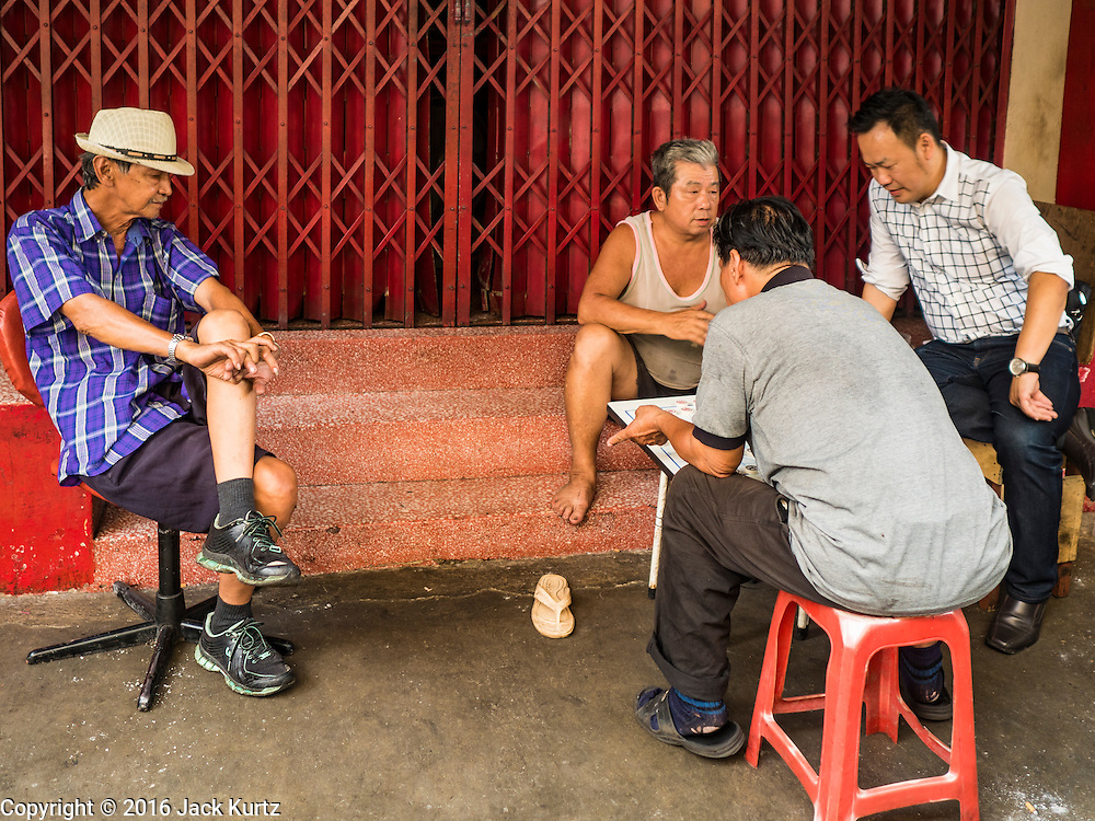 23 MARCH 2016 - BANGKOK, THAILAND: Men play a form of Chinese checkers on the front stoop of a shrine in the Talat Noi section of Bangkok.       PHOTO BY JACK KURTZ