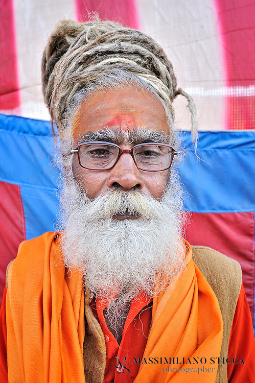 """Sadhu (or Baba) during the Maha Kumbh Mela in Allahabad.....In Hinduism, s?dhu (skt ???? s?dhu, """"good; good man, holy man"""") denotes an ascetic, wandering monk. Although the vast majority of s?dhus are yog?s, not all yog?s are s?dhus. The s?dhu is solely dedicated to achieving mok?a (liberation), the fourth and final a?rama (stage of life), through meditation and contemplation of brahman. S?dhus often wear saffron-colored clothing, symbolizing their sany?sa (renunciation)...This way of life is open to women; the female form of the word is s?dhv? ??????"""
