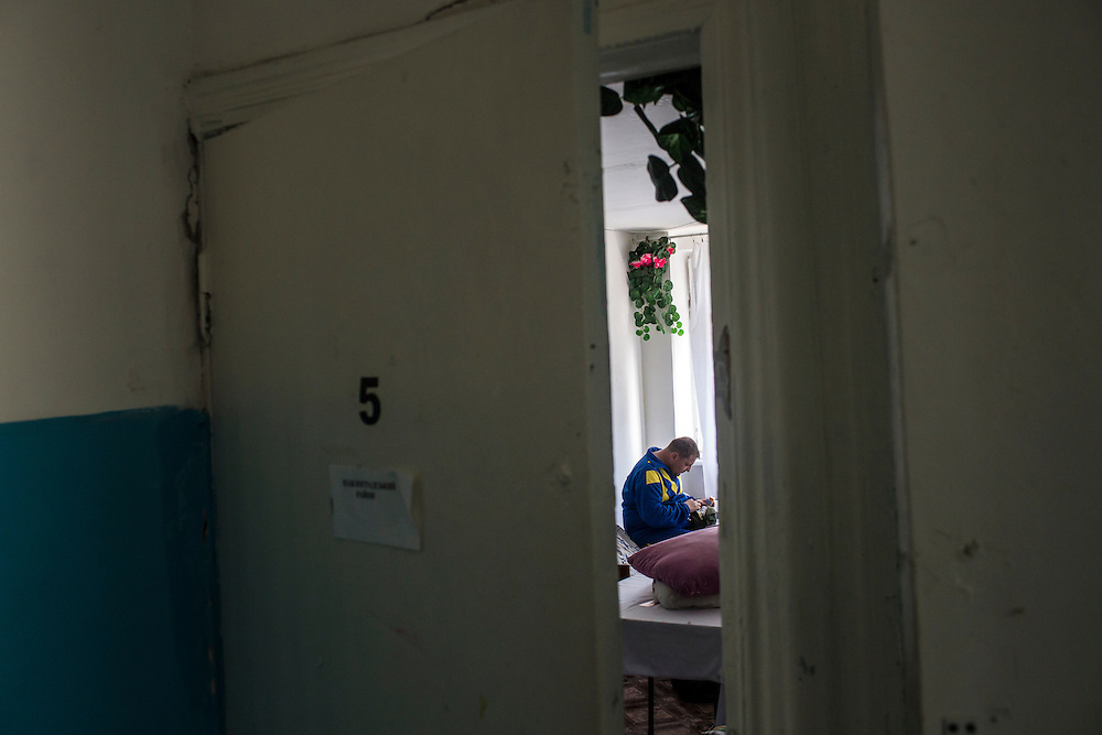DNIPROPETROVSK REGION, UKRAINE - MAY 19: A member of the Donbass Battalion, a pro-Ukrainian militia, sits in his room in the barracks on May 19, 2014 in Dnipropetrovsk Region, Ukraine. A week before presidential elections are scheduled, questions remain whether the eastern regions of Donetsk and Luhansk are stable enough to administer the vote. (Photo by Brendan Hoffman/Getty Images) *** Local Caption ***
