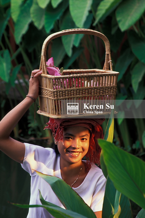 Cambodian girl carrying a basket of lotus flowers on the head, Angkor, Cambodia