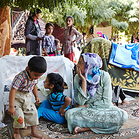 Syrian refugee Peroz Ismail, 27-years-old, sits on a blanket with her children in Quashtapa Park in Quashtapa, Iraq outside of Erbil in Iraqi Kurdistan, Saturday, August 31, 2013. For the past week the family has been living on a blanket with hundreds of other Syrian refugees in a small park on the outskirts of Erbil. August 2013.