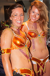 London, August 25th 2014. Two women wait to join the procession after final touch ups to costumes are made, as Notting Hill Carnival goers prepare to party despite the pouring rain.