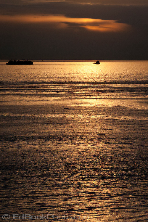 A tugboat tows a barge into the Strait of Juan de Fuca from Admiralty Inlet in Puget Sound past Point Wilson on the Olympic Peninsula of Washington state, USA